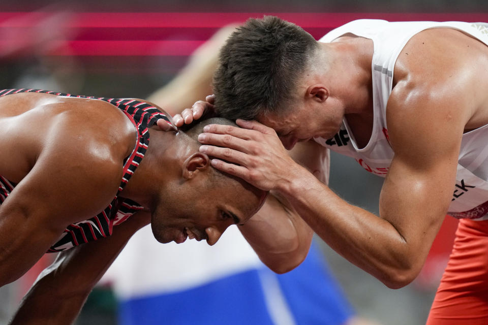 Damian Warner, left, of Canada, celebrates after winning the gold medal in the decathlon with Pawel Wiesiolek, of Poland, at the 2020 Summer Olympics, Thursday, Aug. 5, 2021, in Tokyo.(AP Photo/Petr David Josek)