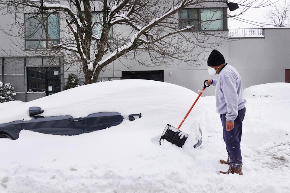 <p>Orlando Flores — who recently moved to Chicago from Texas — digs out his wife's car in Chicago. </p>