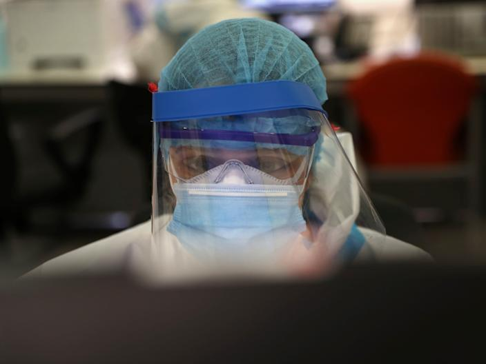 A medical worker in full protective gear works on a computer at the intensive care unit (ICU) of the Infanta Sofia University hospital in Madrid, Spain, May 14, 2020. REUTERS/Susana Vera
