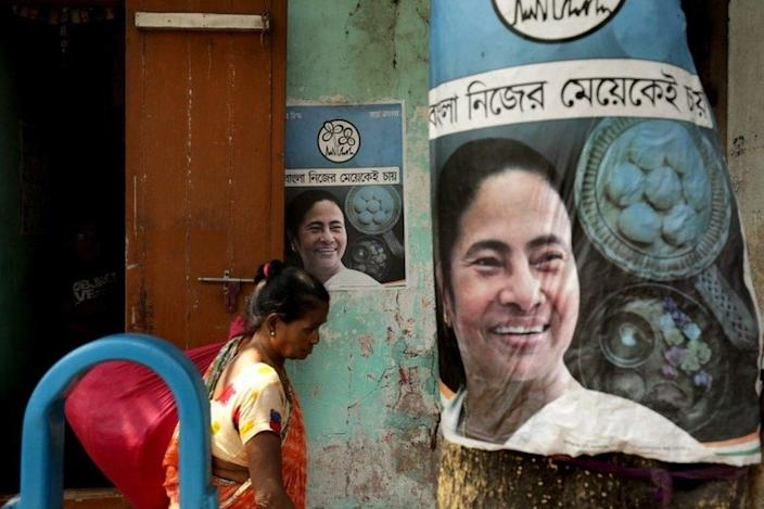 A woman passing the election poster of the All India Trinamool Congress leader and Prime Minister West Bengal Mamatabernergy in Kolkata, India, March 4, 2021