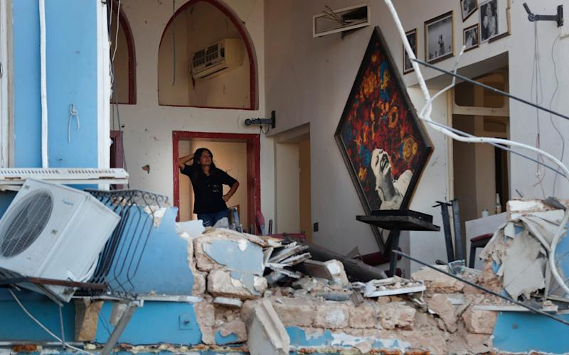 A woman stands inside a damaged restaurant a day after an explosion hit the seaport of Beirut - AP Photo/Hussein Malla