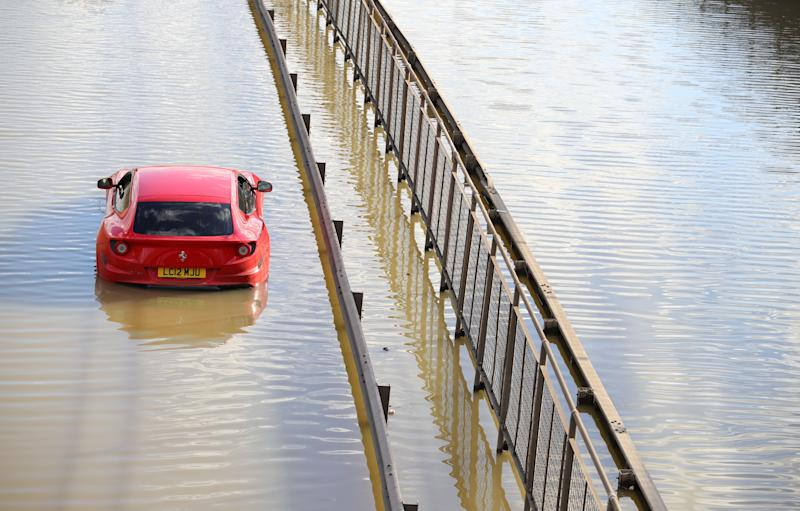 An abandoned Ferrari in flood water on the North Circular road near Brent Cross, north London, after a water main burst. (Photo: PA)