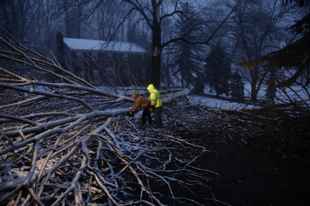 <p>Streets department workers David Boardly, left, and James Ockimey clear a downed tree during a winter storm, Friday, March 2, 2018, in Marple Township, Pa. (Photo: Matt Slocum/AP) </p>
