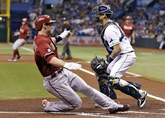 Arizona Diamondbacks' Paul Goldschmidt, left, slides safely home ahead of the throw to Tampa Bay Rays catcher Jose Lobaton, right, during the first inning of an interleague baseball game on Wednesday, July 31, 2013, in St. Petersburg, Fla. Goldschmidt and Martin Prado scored on a two-run single by Cody Ross off Rays starting pitcher Jeremy Hellickson. (AP Photo/Chris O'Meara)
