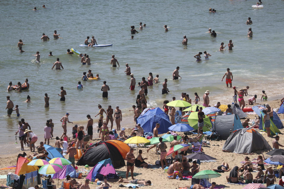 Crowds gather at the water's edge as hot weather draws crowds to the beach in Bournemouth, England, Thursday June 25, 2020. Coronavirus lockdown restrictions are being relaxed but people should still respect the distancing requirements between family groups. According to weather forecasters this could be the UK's hottest day of the year, so far, with scorching temperatures forecast to rise even further. (Andrew Matthews/PA via AP)