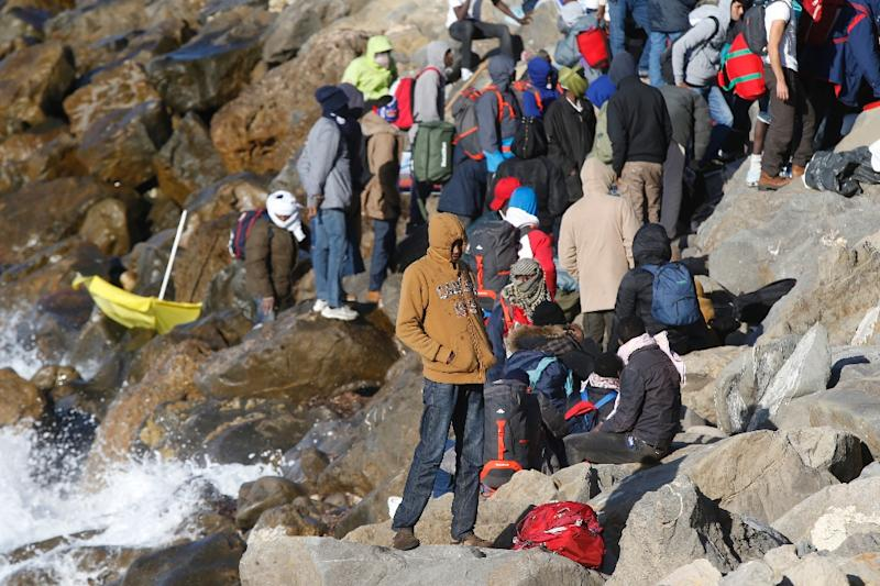 Migrants hide their faces as they wait on the rocks on the shoreline at the French-Italian border in Ventimiglia on September 30, 2015 (AFP Photo/Valery Hache)