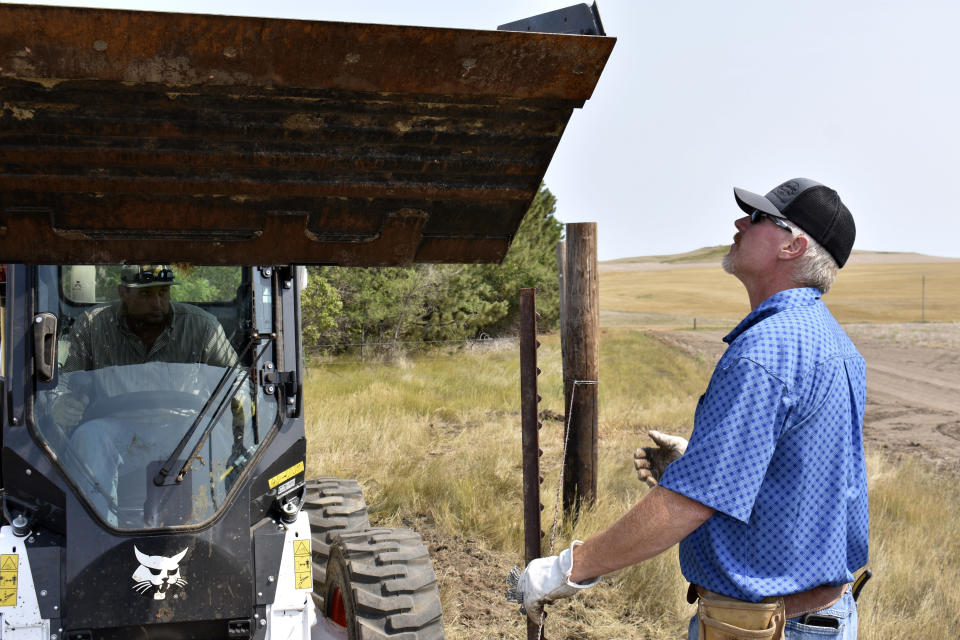 Howdy Lawlar, right holds a steel post as Charlie Lewis, left prepares to use a Bobcat to push it into the ground as they repair a barbed wire fence on Lawlar's farm, Aug. 25, 2021, in McKenzie County, N.D. Lewis came to the county to work in the booming oil fields but now works as Lawlar's farmhand. (AP Photo/Matthew Brown)