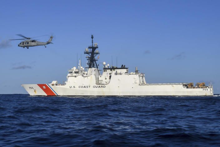In this Aug. 25, 2020 photo provided by the U.S. Navy, an MH-60S Sea Hawk Helicopter hovers next to the Legend-class cutter USCGC Munro in the Pacific Ocean. The Coast Guard cutter Munro had just embarked on a national security mission to patrol the maritime boarder between the United States and Russia in late June 2020, when one of its guardsman was diagnosed with COVID-19. Contract tracing led to more than a dozen other members of the ship's crew being ordered into quarantine for two weeks. (Mass Communication Specialist 3rd Class Madysson Anne Ritter/U.S. Navy via AP)