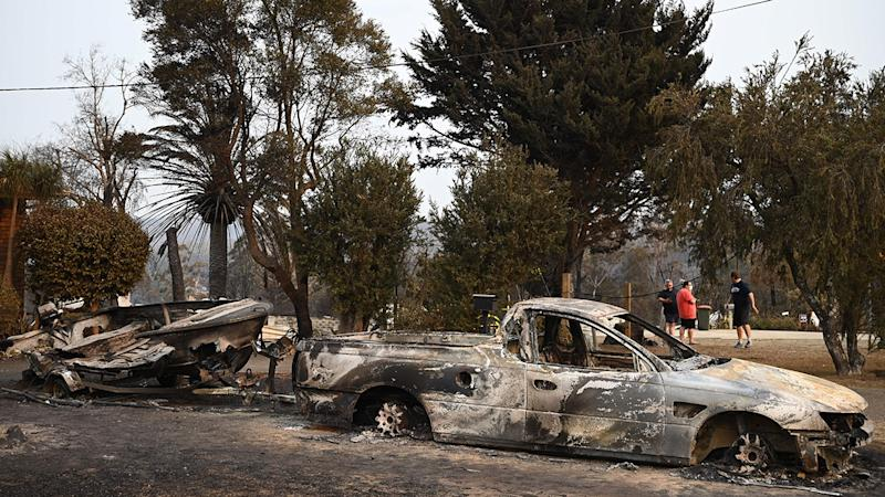 Vehicles gutted by bushfires, pictured here in the town of Lake Conjola.