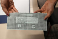 A woman shows her ballot for the abortion referendum at a polling station in San Marino, Sunday, Sept. 26, 2021. Tiny San Marino is one of the last countries in Europe which forbids abortion in any circumstance — a ban that dates from 1865. Its citizens are voting Sunday in a referendum calling for abortion to be made legal in the first 12 weeks of pregnancy. (AP Photo/Antonio Calanni)
