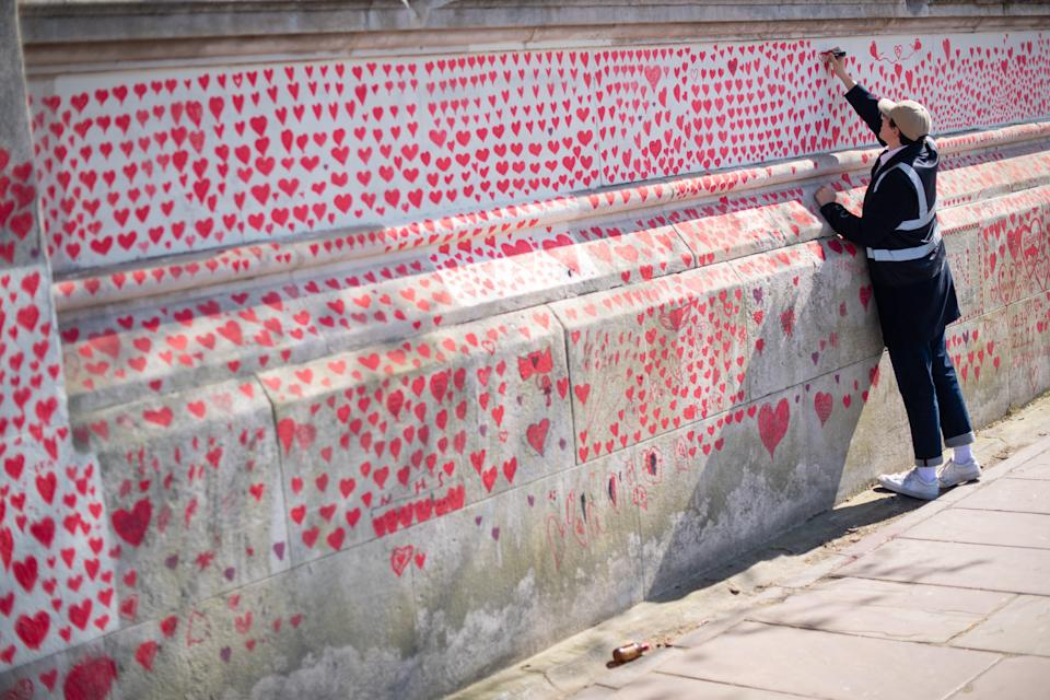 <p>A volunteer adds hearts to the Covid memorial wall in Westminster</p> (PA)