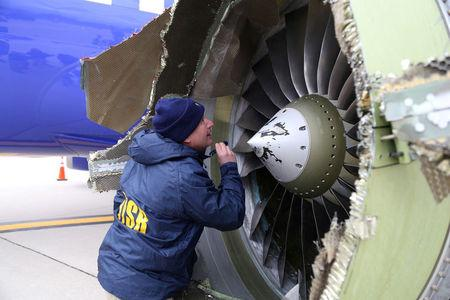FILE PHOTO: A NTSB investigator on scene examining damage to the engine of the Southwest Airlines plane in Philadelphia