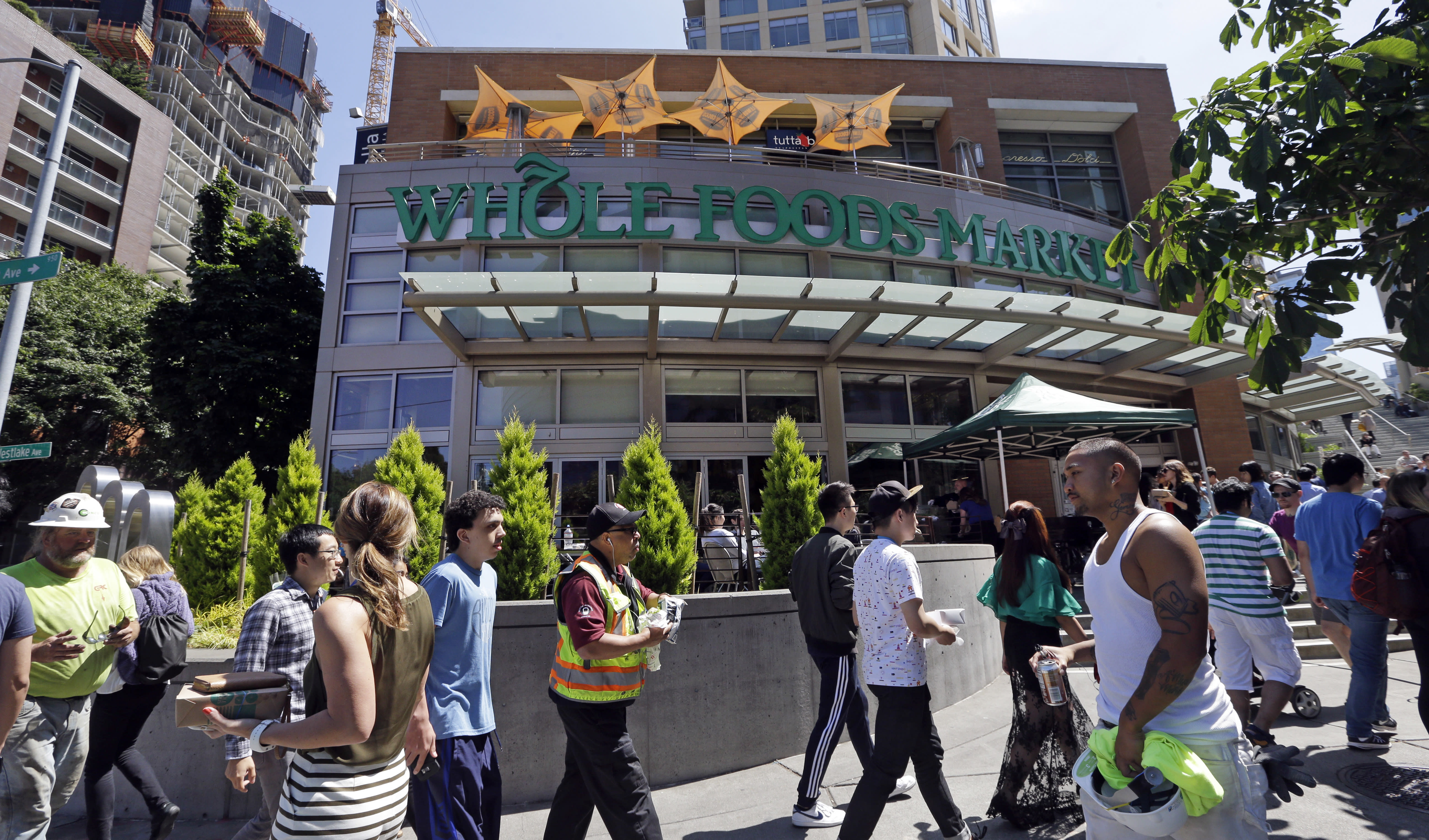 Pedestrians walk past a Whole Foods Market,