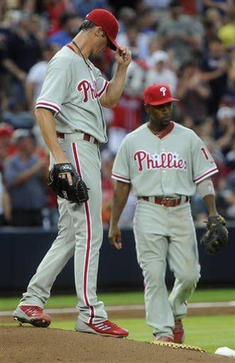 Philadelphia Phillies pitcher Cole Hamels, left, walks back to the mound as shortstop Jimmy Rollins approaches after the Atlanta Braves scored two runs to go ahead during the second inning of a baseball game, Friday, July, 27, 2012, in Atlanta. (AP Photo/John Amis)