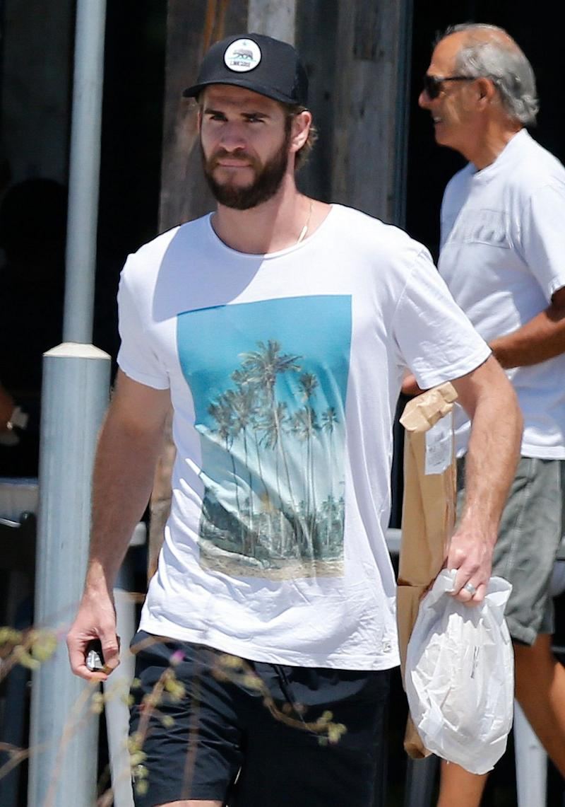 The younger brother of actor Chris Hemsworth holds onto some purchases from his grocery run. Source: Mega