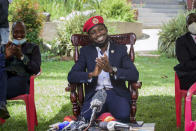 Opposition presidential challenger Bobi Wine smiles as he speaks to the media outside his home, in Magere, near Kampala, in Uganda, Tuesday, Jan. 26, 2021. An attorney for Bobi Wine says Ugandan soldiers have withdrawn from the opposition presidential challenger's home the day after a judge ruled that his house arrest was unlawful. But the attorney tells The Associated Press that security forces can still be seen in the village near the candidate's property outside the capital, Kampala. (AP Photo/Nicholas Bamulanzeki)
