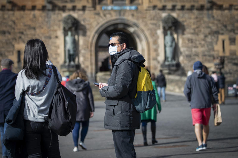 A visitor at Edinburgh Castle wears a protective face mask as the Government's top scientist warmed that up to 10,000 people in the UK are already infected.