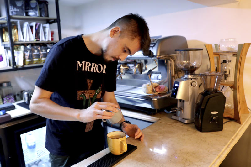 """In this Monday, Oct. 7, 2019 photo, Hamed Azar, a 25-year-old Afghan refugee, makes coffee for customers at his basement Tehran coffee shop in downtown Tehran, Iran. Azar and his business partner, 21-year-old Afghan refugee Fatemeh Jafari, raised money from their parents, as well as used their own cash to open their Telma, or """"Dream,"""" Café and hope it will help bridge the divides and xenophobia Afghans can face in Iran. (AP Photo/Ebrahim Noroozi)"""