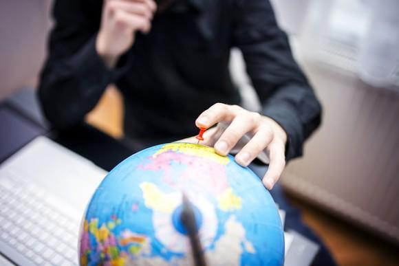 A person sticks a pin in the United States on a globe.