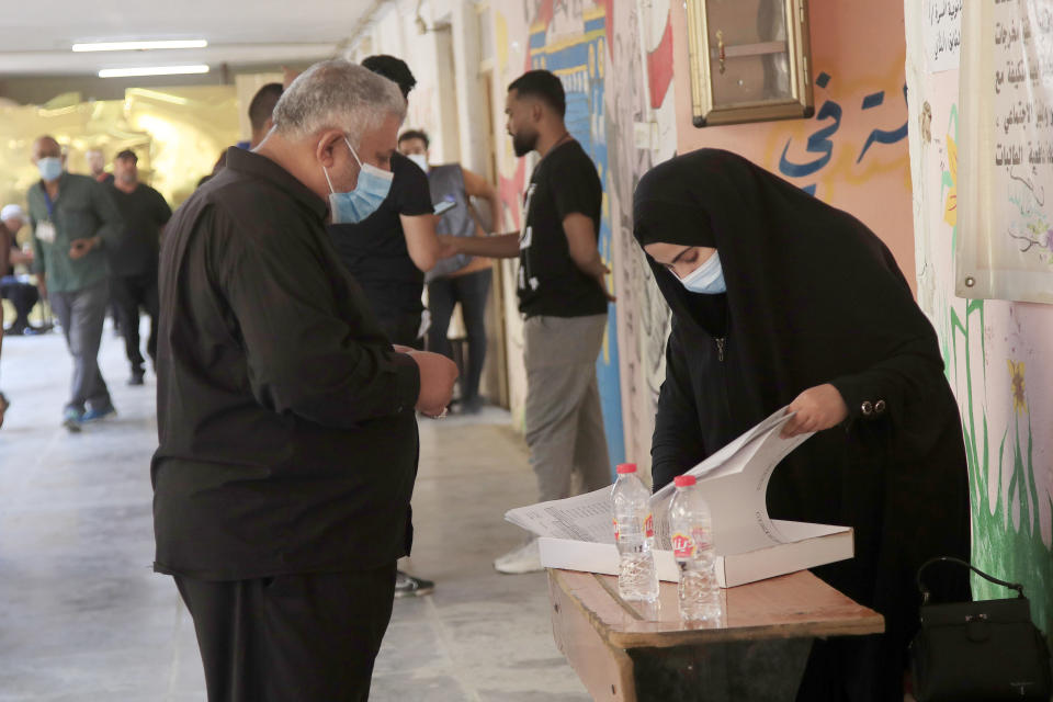 Iraqis voters gather to cast their vote at a ballot station in the country's parliamentary elections in Baghdad, Iraq, Sunday, Oct. 10, 2021. Iraq closed its airspace and land border crossings on Sunday as voters headed to the polls to elect a parliament that many hope will deliver much needed reforms after decades of conflict and mismanagement.. (AP Photo/Hadi Mizban)