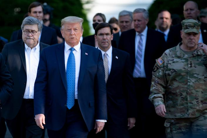 President Donald Trump walks with Attorney General William Barr, left, Secretary of Defense Mark Esper and others from the White House to visit St. John's Church after the area was cleared of people protesting the death of George Floyd in Washington, June 1, 2020.