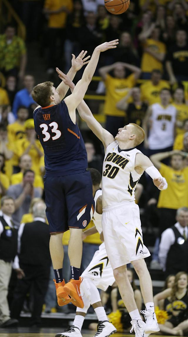 Illinois forward Jon Ekey, left, shoots a 3-point basket over Iowa forward Aaron White (30) during the final seconds of an NCAA college basketball game on Saturday, March 8, 2014, in Iowa City, Iowa. Ekey made the basket to give Illinois a 66-63 victory. (AP Photo/Charlie Neibergall)