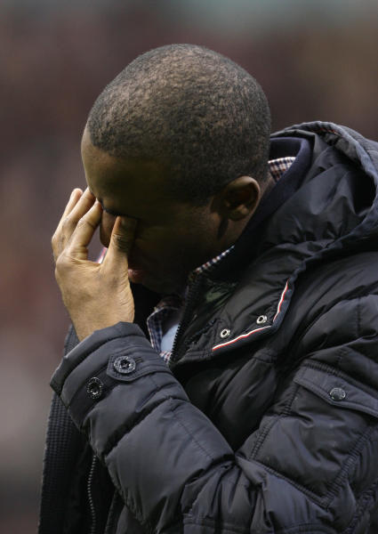 Bolton's Fabrice Muamba wipes tears from his eyes as he returns to The Reebok Stadium before his team's English Premier League soccer match against Tottenham, in Bolton, England, Wednesday, May 2, 2012. (AP Photo/Jon Super)