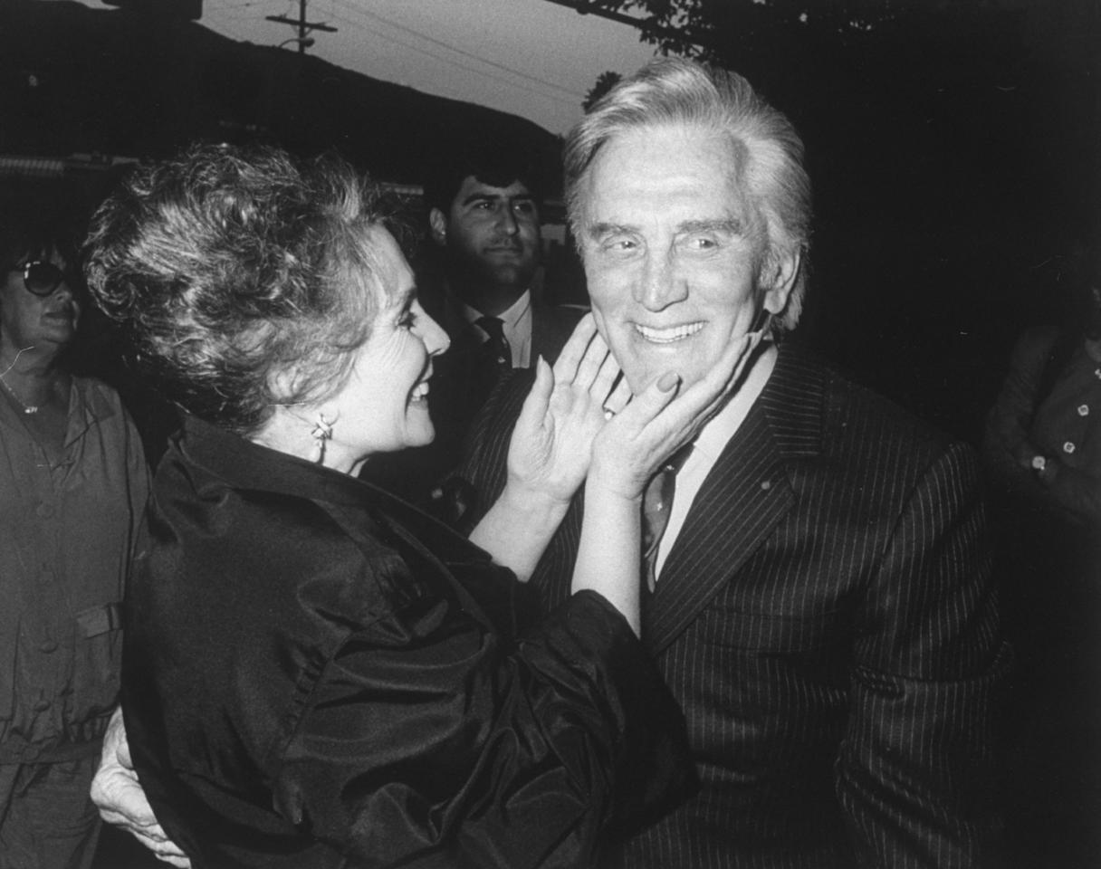 Actress Jean Simmons clasping co-star Kirk Douglas's chin at premiere of their restored 1960 film Spartacus.  (Photo by Kevin Winter/DMI/The LIFE Picture Collection via Getty Images)