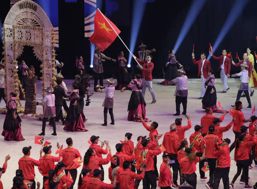 A Vietnam delegate holds a flag during the opening ceremony of the 30th South East Asian Games at the Philippine Arena, Bulacan province, northern Philippines on Saturday, Nov. 30, 2019. (AP Photo/Aaron Favila)