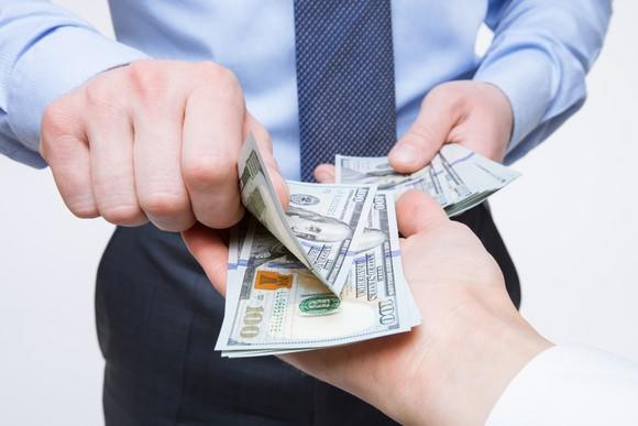 Businessman handing money to another person