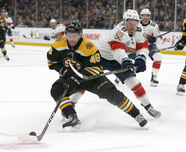 Boston Bruins defenseman Matt Grzelcyk (48) controls the puck ahead of Florida Panthers center Jayce Hawryluk (8) during the first period of an NHL hockey game, Saturday, March 30, 2019, in Boston. (AP Photo/Mary Schwalm)