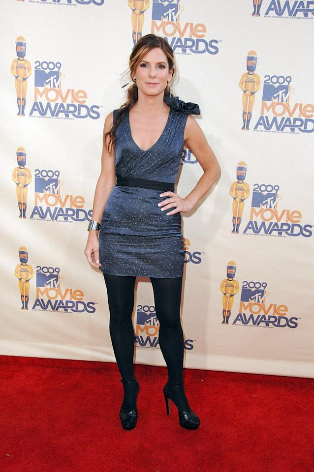 "<a href=""http://movies.yahoo.com/movie/contributor/1800018970"">SANDRA BULLOCK</a>  Grade: C  Sandra's ensemble has a number of different little touches, none of which work. The scoop neck, the belt, the line, the shoulder bow, and especially the tights. The navy blue color isn't bad, though."