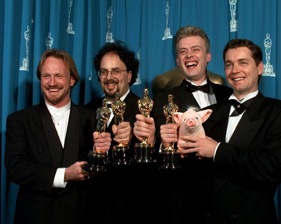 "Left to right, Scott E. Anderson, Charles Gibson, Neal Scanlan and John Cox smile for photographers backstage after winning for Best Achievement in Visual Effects for ""Babe"", at the 68th Academy Awards at the Music Center in Los Angeles, Monday, March 25, 1996. (AP Photo/Reed Saxon)"