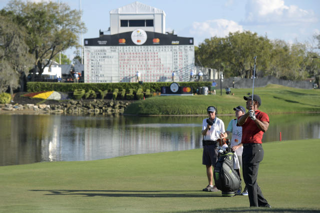 Tiger Woods, right, watches his shot to the 18th green during the final round of the Arnold Palmer Invitational golf tournament Sunday, March 18, 2018, in Orlando, Fla. (AP Photo/Phelan M. Ebenhack)
