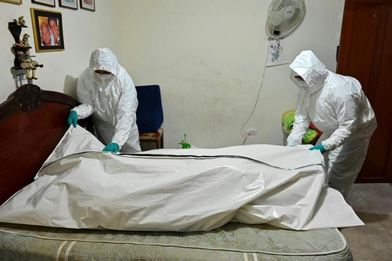 Funeral home workers prepare to carry the corpse of a man who died allegedly from COVID-19 from his home in Cali, Colombia, in July 2020