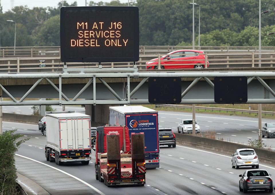 Lorries drive past a fuel warning sign on the M1 motorway amid a fuel shortage, in Luton