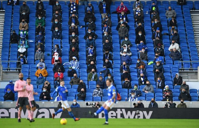 Fans wearing face masks sit socially distanced during an English Premier League football match