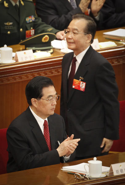 Chinese Premier Wen Jiabao, right, walks near Chinese President Hu Jintao on his way to deliver the opening speech during the opening session of the National People's Congress in Beijing's Great Hall of the People, China, Monday, March 5, 2012.(AP Photo/ Vincent Thian)