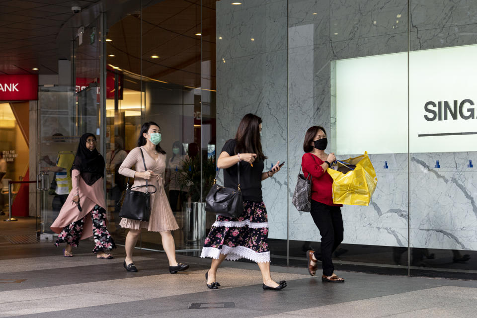 SINGAPORE, SINGAPORE - APRIL 6: Office workers wearing protective face masks carry their belongings on their way home from the financial district on April 6, 2020 in Singapore, a day before a 'circuit breaker' takes effect. The Singapore government will close all schools and most workplaces and limit social interactions and movement outside homes for at least a month to stem the spike in local coronavirus cases.(Photo by Ore Huiying/Getty Images)