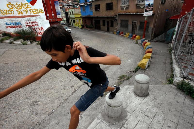 "A boy plays in front of a graffiti that reads in Spanish ""Chavez, heart of my homeland"" at the neighborhood of Petare in Caracas, Venezuela, Monday, Dec. 17, 2012. Smarting after a bruising loss in state elections, Venezuela's opposition will now be forced to reassess its strategy and rebuild quickly to prepare for presidential elections that many expect could be called to replace ailing leftist President Hugo Chavez. (AP Photo/Fernando Llano)"