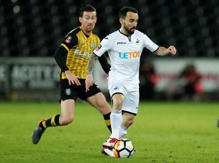 FILE PHOTO: Soccer Football - FA Cup Fifth Round Replay - Swansea City vs Sheffield Wednesday - Liberty Stadium, Swansea, Britain - February 27, 2018 Swansea City's Leon Britton in action with Sheffield Wednesday's David Jones Action Images via Reuters/Andrew Boyers