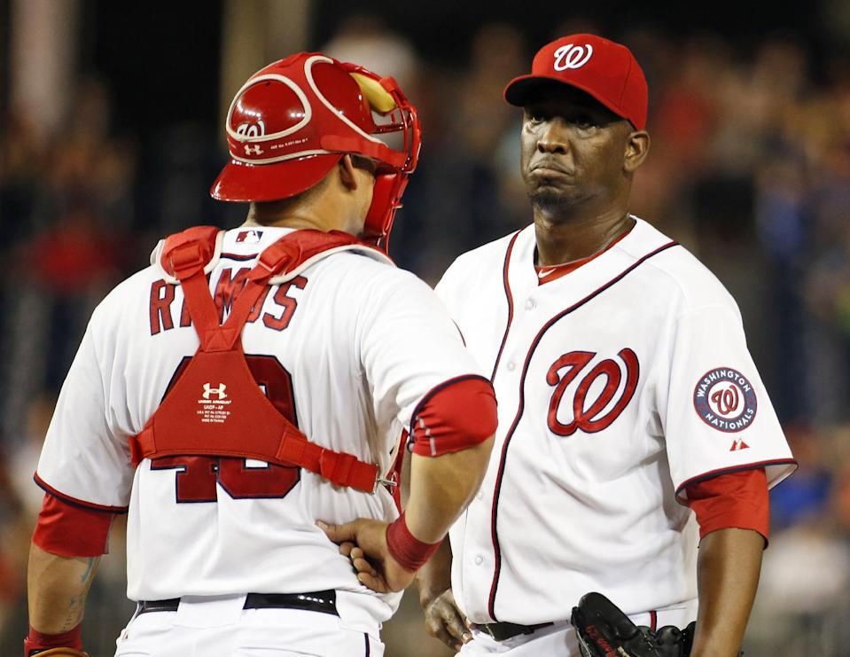 Washington Nationals catcher Wilson Ramos (40) talks with relief pitcher Rafael Soriano during the ninth inning of a baseball game against the Philadelphia Phillies at Nationals Park, Friday, Sept. 5, 2014, in Washington. The Phillies won 9-8 in 11 innings. (AP Photo/Alex Brandon)