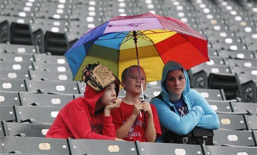 Evan Browning, 13, left, Riley Boren, 12, and Michelle Wilde sit under an umbrella during a rain delayed start of the baseball game between the Los Angeles Angels and Texas Rangers Saturday, Sept. 29, 2012, in Arlington, Texas. (AP Photo/LM Otero)