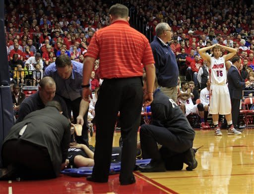 Dayton's Matt Derenbecker (15) looks on in concern as paramedics attend to Butler's Rontei Clarke during the first half of an NCAA college basketball game, Saturday, Jan. 12, 2013, in Dayton, Ohio. Derenbecker was called for an intentional foul on Clarke, who was carried from the floor on a backboard. (AP Photo/Skip Peterson)