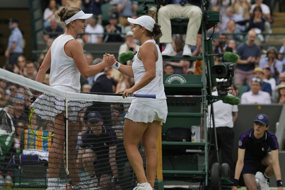 Australia's Ashleigh Barty, right, holds hands with Czech Republic's Barbora Krejcikova after winning the women's singles fourth round match on day seven of the Wimbledon Tennis Championships in London, Monday, July 5, 2021. (AP Photo/Alastair Grant)
