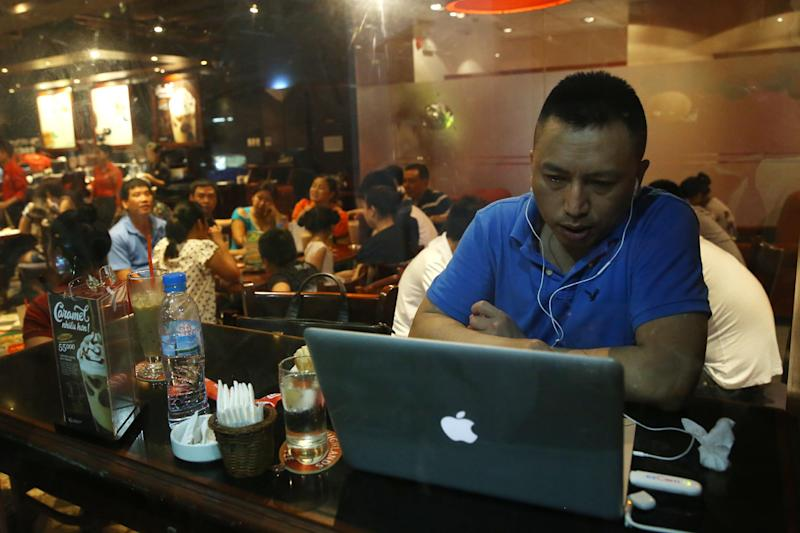 A Vietnamese man uses a laptop to go online by a 3G device inserted into a USB pot at a cafe in Ha Noi, Viet Nam on Wednesday, May 14, 2013. Close to a third of Vietnam's 90 million people are online and men and women browsing phones and tablets are ubiquitous in the cafes of its towns and cities. The country's potential for growth, young population and good Internet infrastructure have made it an attractive destination for regional and international investors and startups in content provision, e-payment and other services. (AP Photo/Na Son Nguyen).