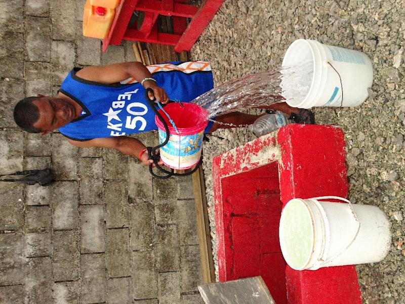 A resident fills buckets from a well in Majuro, Marshall Islands (AFP Photo/Giff Johnson)