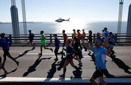 Athletics - New York City Marathon - New York City, New York, U.S. - November 4, 2018 Runners cross the Verrazzano Bridge as a helicopter hovers nearby during the marathon REUTERS/Andrew Kelly