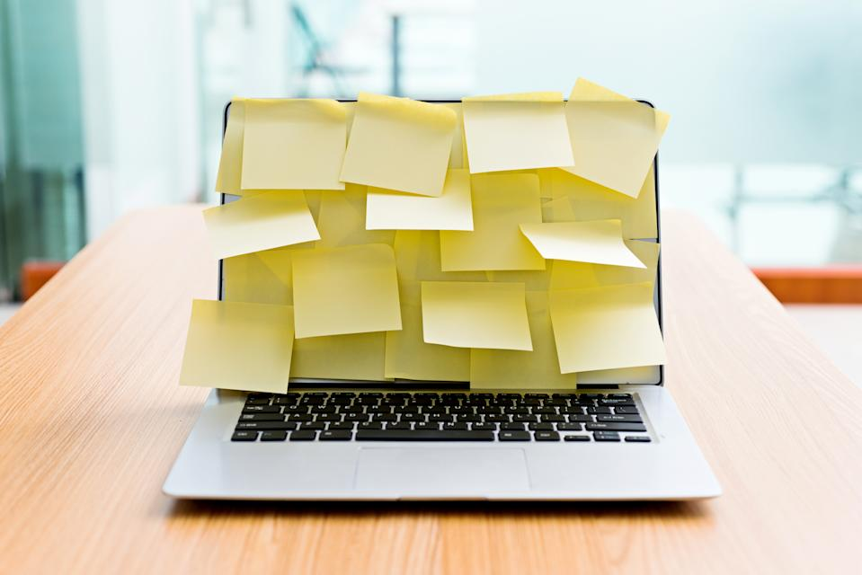 Laptop screen covered by group of yellow adhesive notes