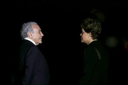 Brazil's Vice President Michel Temer talks with Brazil's President Dilma Rousseff as they await the arrival of German Chancellor Angela Merkel before a dinner at the Alvorada Palace in Brasilia